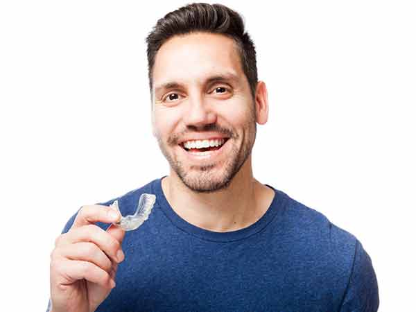 Man holding clear aligner removable orthodontic appliance