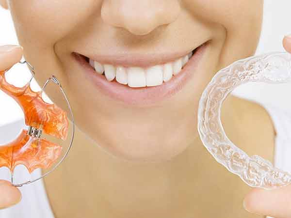 Woman holding Hawley and clear Essix type removable retainers