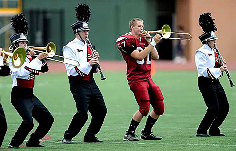 Football player playing trombone in high school marching band