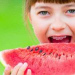 Girl wearing braces eating watermelon