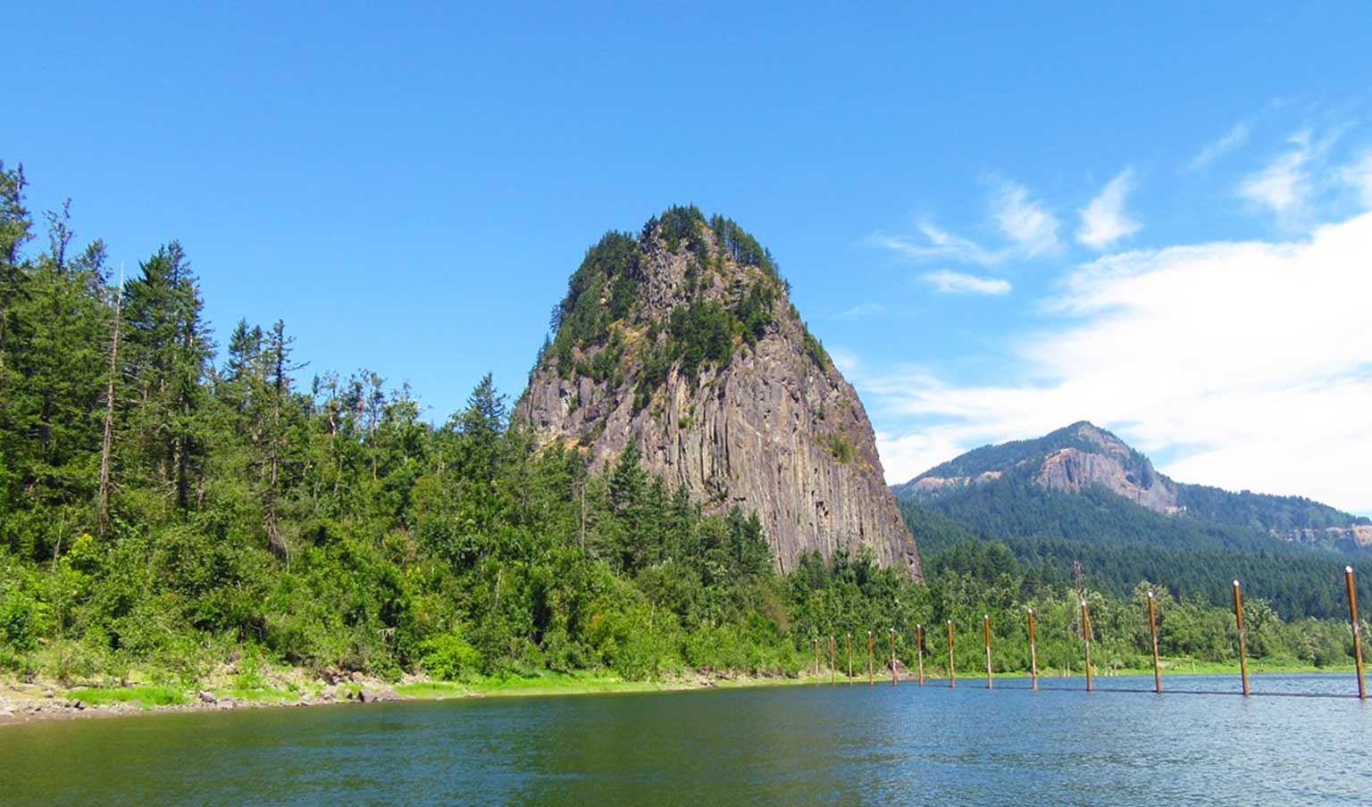 Beacon Rock State Park, a short drive from Vancouver WA is pictured with beacon rock towering above the trees and the Columbia River in the foreground