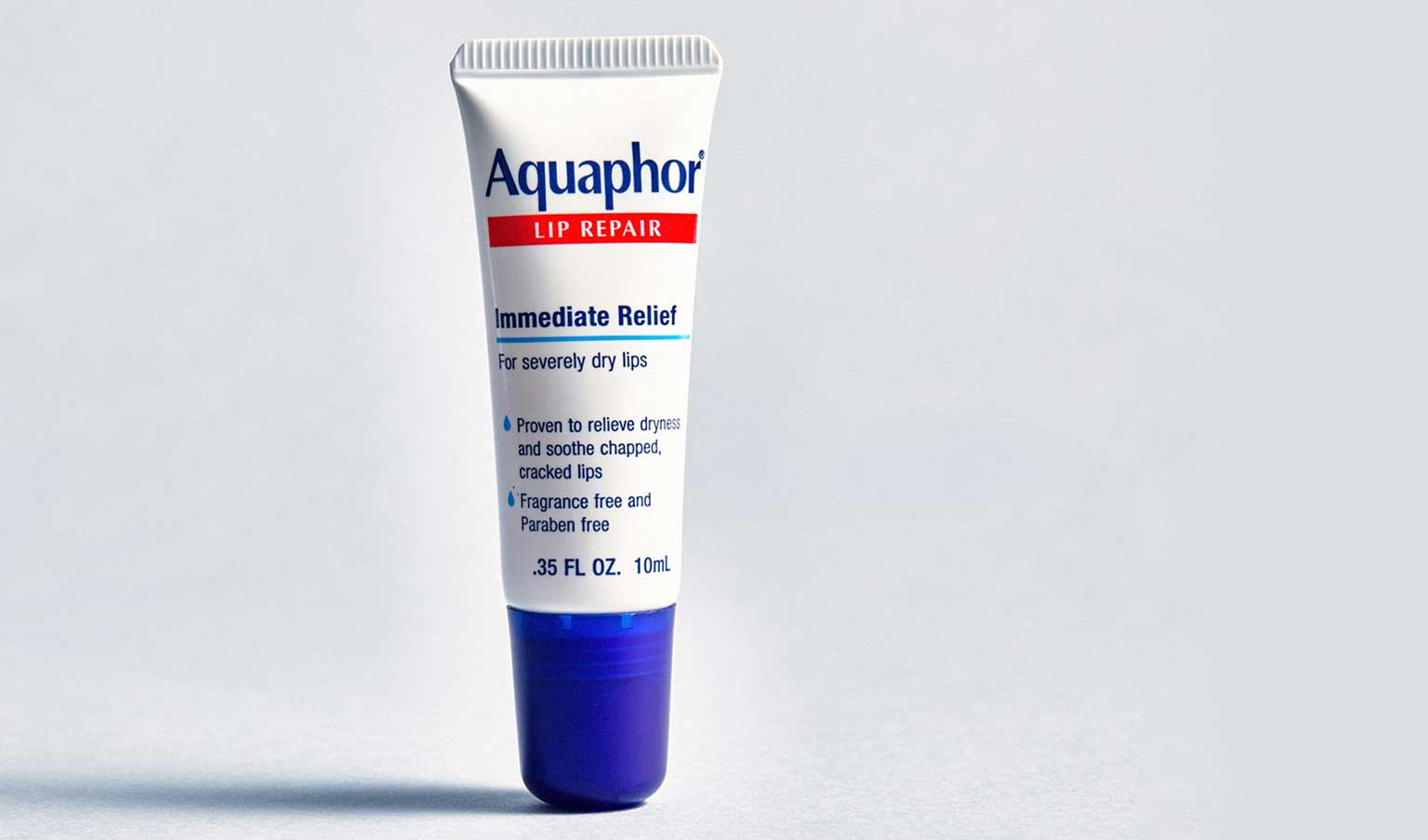 tube of Aquaphor lip repair on light grey background