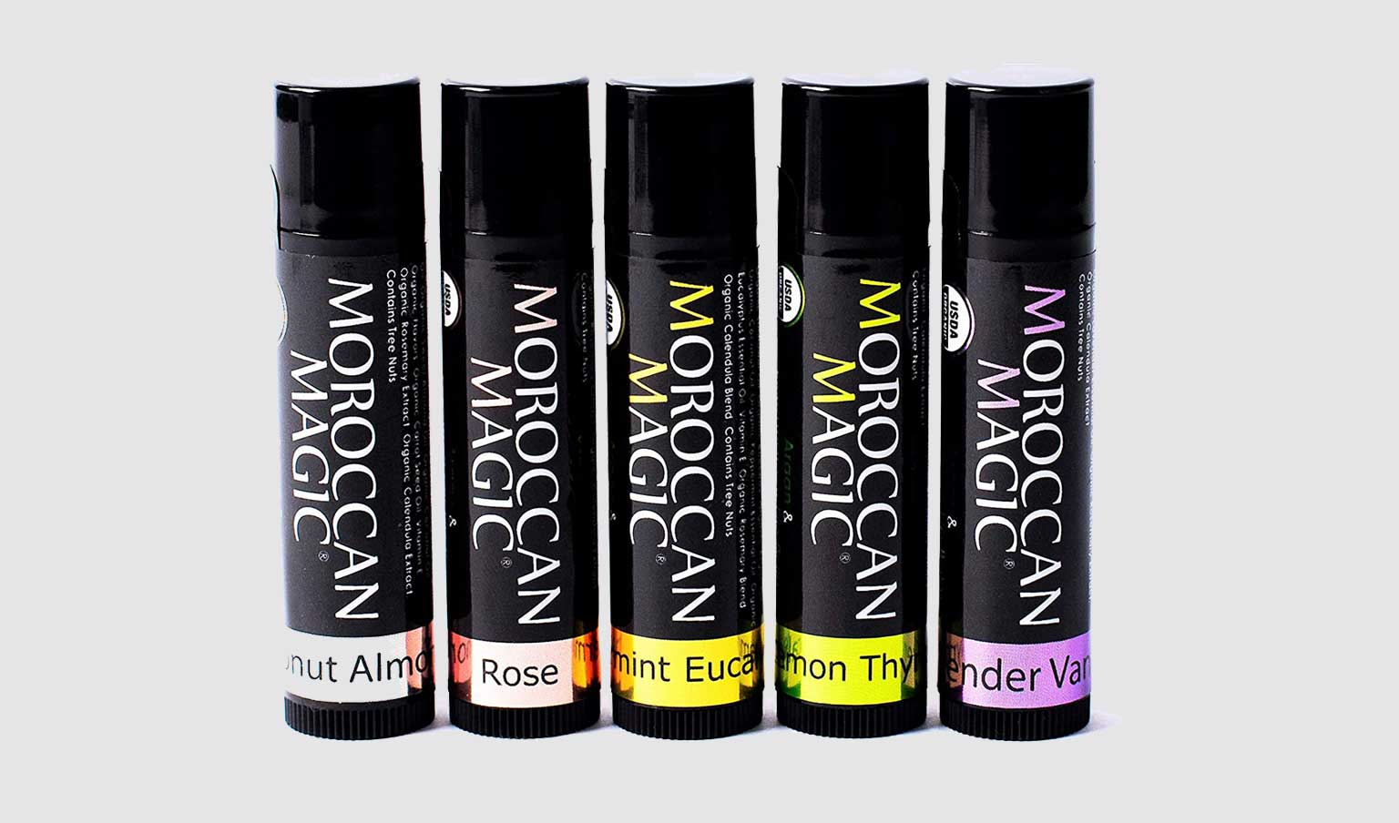 5 varieties of Moroccan Magic lip balm on a light grey background