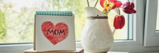 Celebrate Mother's Day 2021 in Vancouver, WA-vignette with a small, spiral-bound notebook standing on top of some old books with a red heart with Mom written inside of it on the page. Next tot he notebook is a white ceramic vase containing a few red and yellow flowers.