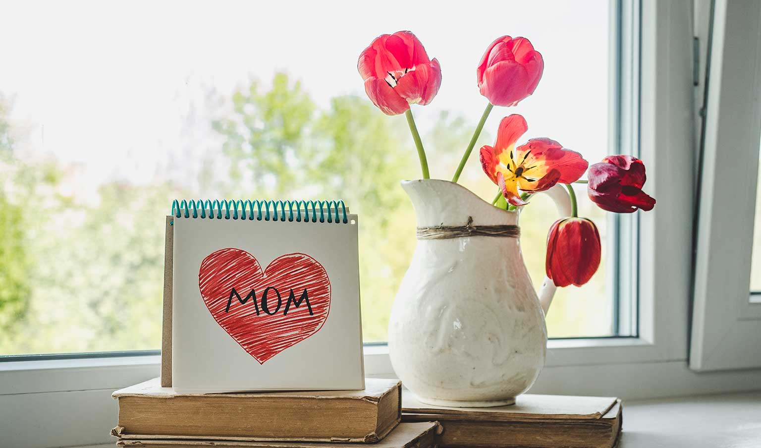 Places to celebrate Mother's Day 2021 in Vancouver, WA -vignette with a small, spiral-bound notebook standing on top of some old books with a red heart with Mom written inside of it on the page. Next to the notebook is a white ceramic vase containing a few red and yellow flowers.